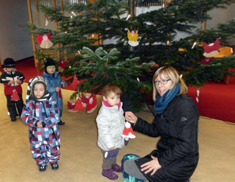 Kindergartenkinder schmücken Tannenbaum in Volksbank-Filiale